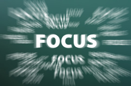 Focus word with motion rays on green chalkboard background